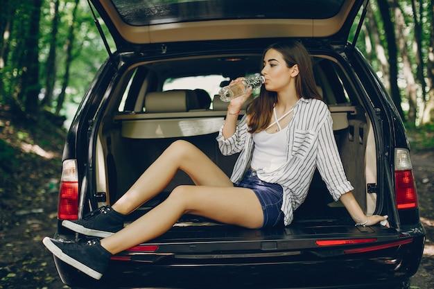 Mädchen in einem sommerpark nahe auto