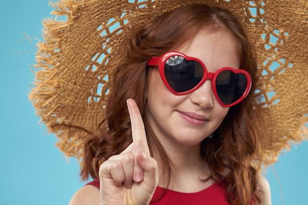 Mädchen in einem strand strohhut in sonnenbrille lockiges haar spaß blau