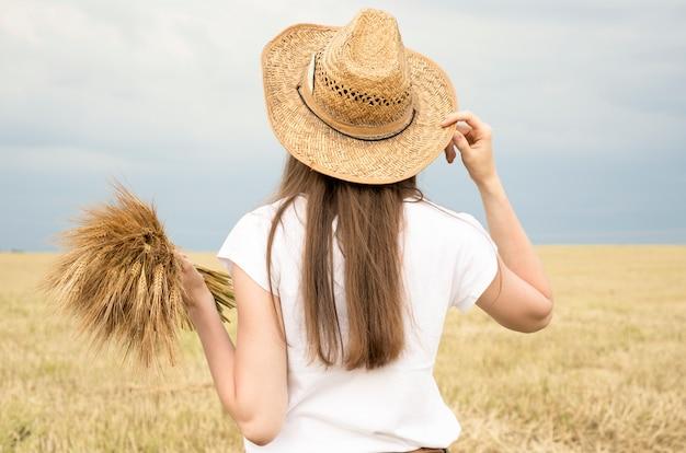 Mädchen in einem strohhut, der mit ihrem rücken in der mitte eines weizenfeldes steht und sommerferien in der landschaft genießt.