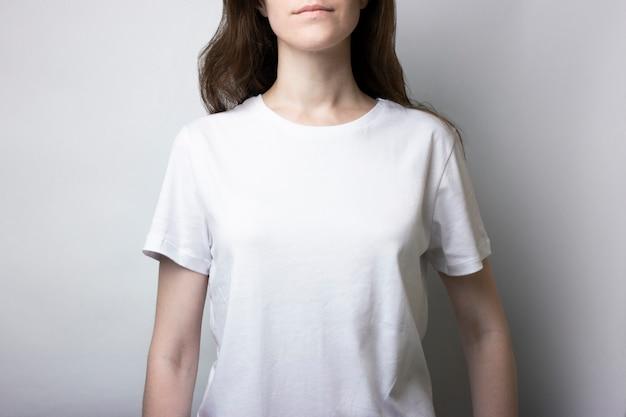Mädchen in einem t-shirt, das auf einem neutralen steht. leer für branding. monochromes modell