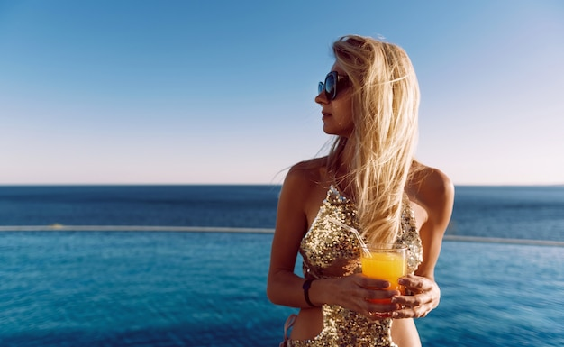 Mädchen in einem teuren badeanzug mit einem cocktail in der hand verbringt ihren urlaub in der nähe des pools im resort