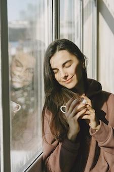 Mädchen in einem warmen mantel nahe fenster mit einer tasse kaffee