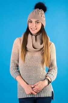 Mädchen in einem warmen pullover, schal und mütze auf einem blauen hintergrund Premium Fotos