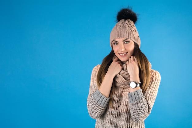 Mädchen in einem warmen pullover, schal und mütze auf einem blauen hintergrund