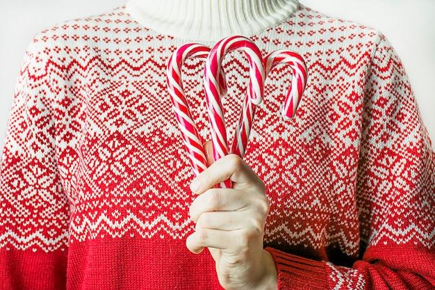 Mädchen in einem weihnachtspullover hält weihnachtszuckerstangen auf einem weißen hintergrund, nahaufnahme.