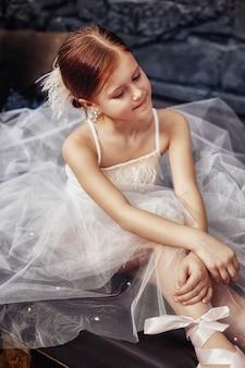 Mädchen in einem weißen ballkleid und in schuhen, schönes rotes haar. junge theaterschauspielerin. kleines primaballett. junges ballerinamädchen bereitet sich für eine ballettleistung vor