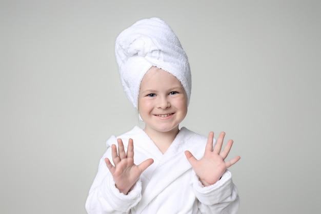 Mädchen in einem weißen gewand und einem handtuch auf dem kopf nach dem duschen und waschen ihrer haare. kinderkosmetik und hautpflege, spa-behandlungen. sauberes und schönes haar.