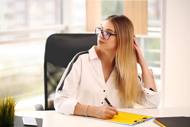 Mädchen in einem weißen hemd, das im büro sitzt, student.