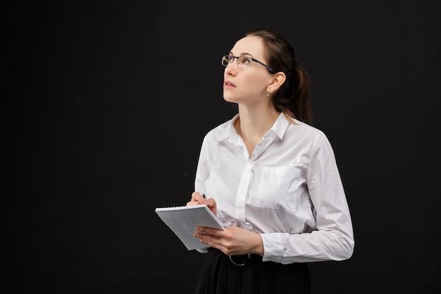 Mädchen in einem weißen hemd kommt mit ideen auf einem schwarzen raum auf.