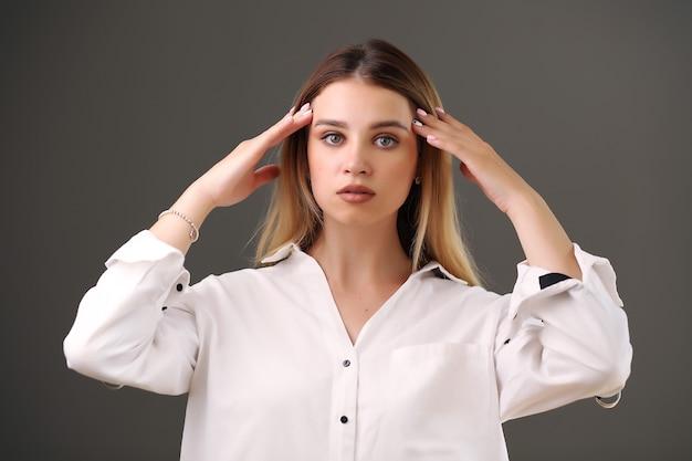 Mädchen in einem weißen hemd posiert auf grauem hintergrund im studio.