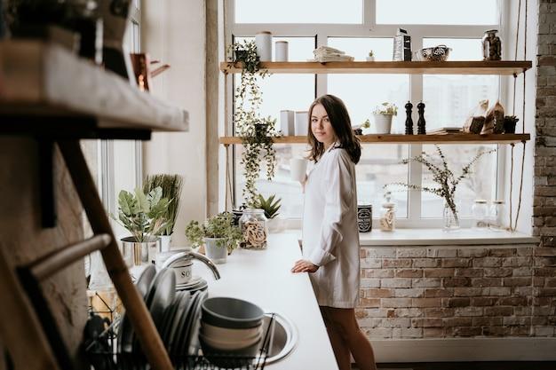 Mädchen in einem weißen hemd trinkt kaffee morgens in einer küche.