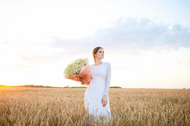 Mädchen in einem weißen kleid bei sonnenuntergang