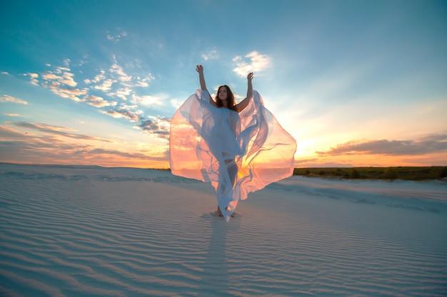 Mädchen in einem weißen kleid der fliege tanzt und wirft in der sandwüste bei sonnenuntergang auf