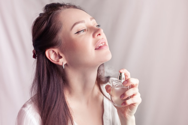 Mädchen in einem weißen kleid sprüht sich parfüm auf ihren hals
