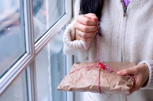 Mädchen in einem weißen pullover mit einem geschenk und einem kerzenhalter in den händen, zu hause im wohnzimmer am fenster