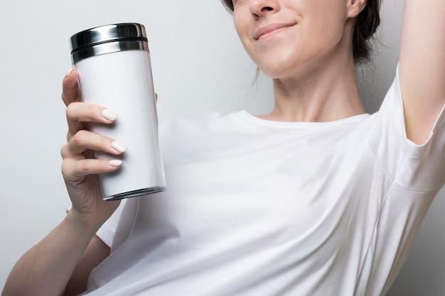 Mädchen in einem weißen t-shirt hält einen thermocup mit kaffee. leer für branding. monochromes modell