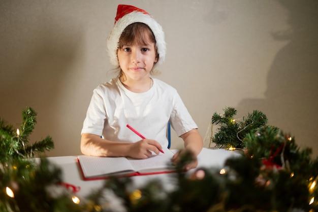 Mädchen in einem weißen t-shirt mit einem roten stift und einer neujahrsmütze auf dem kopf schreibt dem lieben weihnachtsmann einen brief an den tisch in erwartung der geburt. wunschliste mit geschenken für das neue jahr.