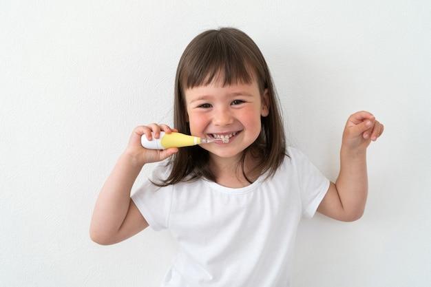 Mädchen in einem weißen t-shirt putzt sich die zähne mit einer elektrischen bürste