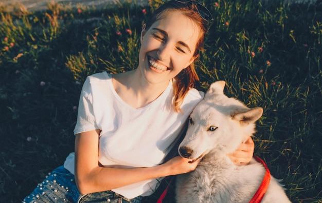 Mädchen in einem weißen t-shirt spielt mit ihrem hund