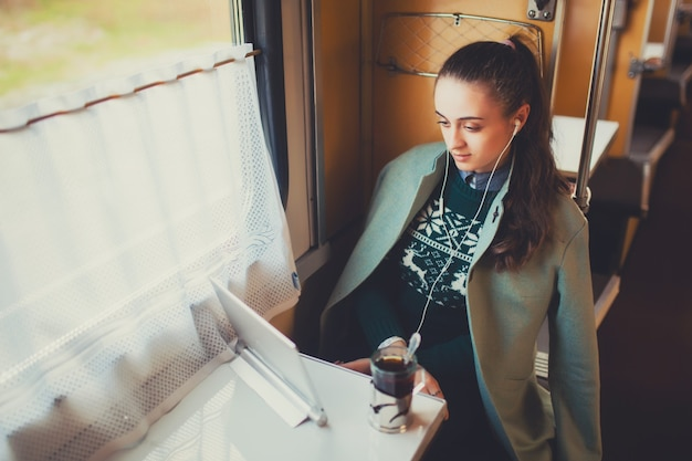 Mädchen in einem zug mit einem laptop, der einen film sieht und tee trinkt. reisen
