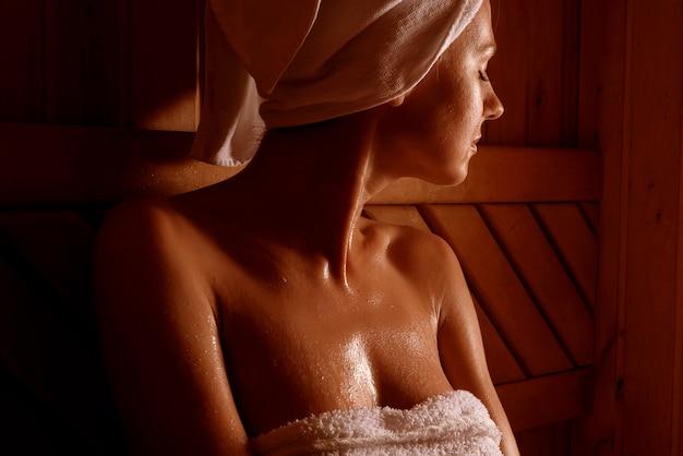 Mädchen in einer badekur in einer traditionellen sauna mit einer bürste für haut und einem waschlappen.