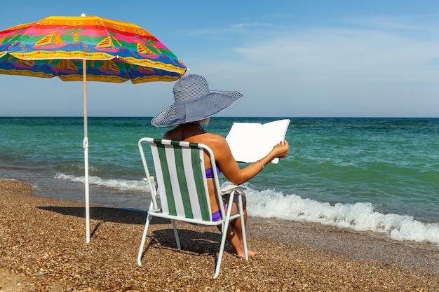 Mädchen in einer chaiselongue in der nähe eines sonnenschirms am strand liest eine zeitschrift
