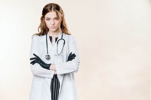Mädchen in einer doktorklage auf einer hellen monophonen wand