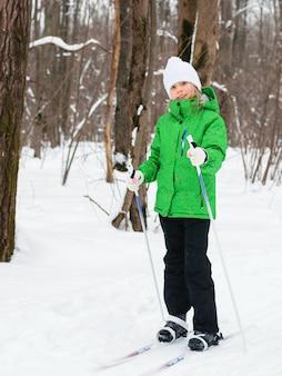 Mädchen in einer grünen jacke, die beim skifahren im winterwald aufwirft.