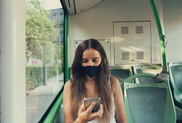 Mädchen in einer maske, die ihr handy im stadtbus betrachtet
