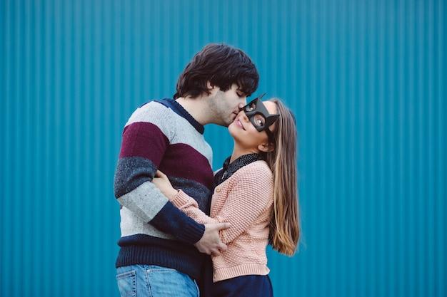 Mädchen in einer maske ihren jungen kerl küssend.