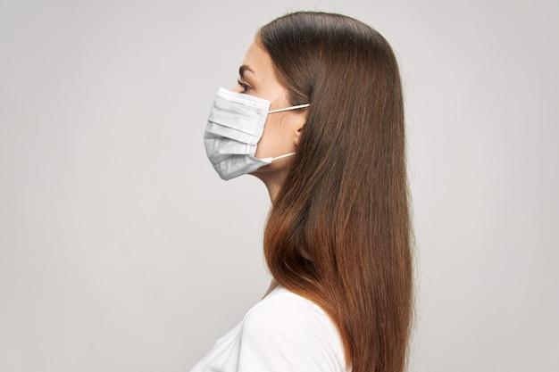Mädchen in einer medizinischen gesichtsmaske in der seitenansicht