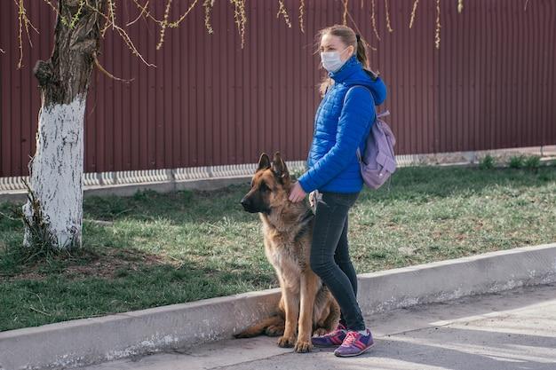 Mädchen in einer medizinischen schutzmaske geht mit einem hund auf die straße. freizeit mit einem haustier während der quarantäne. gehen sie mit einem deutschen schäferhund. selbstisolationsmodus