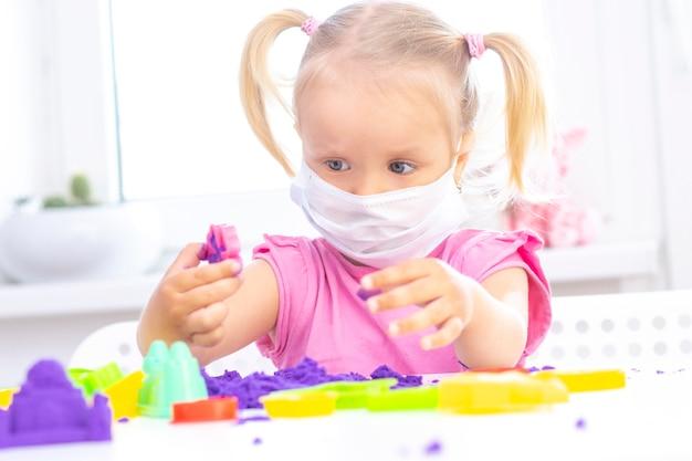 Mädchen in einer medizinischen schutzmaske spielt kinetischen sand in quarantäne. blondes schönes mädchen lächelt und spielt mit lila sand auf einem weißen tisch. coronavirus pandemie
