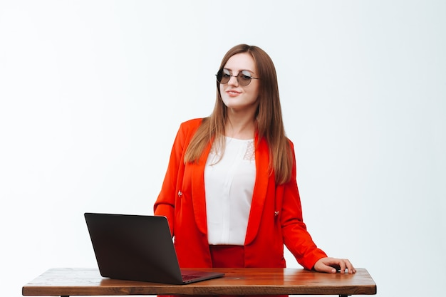 Mädchen in einer roten jacke, die am computer auf weißem hintergrund arbeitet
