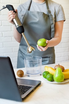 Mädchen in einer schürze hält einen mixer und einen apfel. fruchtsmoothies nach einem rezept aus dem internet zubereiten.