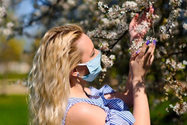 Mädchen in einer schützenden medizinischen maske im frühjahr unter dem blühenden garten