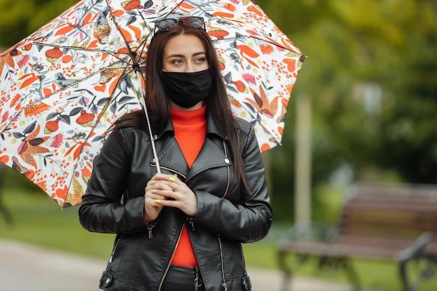 Mädchen in einer schutzmaske geht in den park mit einem regenschirm im regen coronavirus-infektion covid