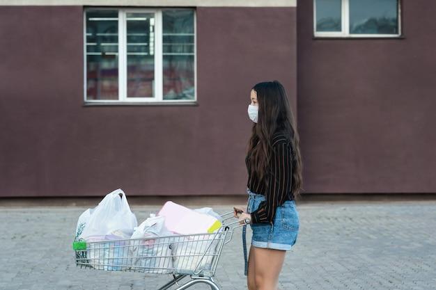 Mädchen in einer schutzmaske rollt einen wagen mit lebensmitteln aus einem supermarkt
