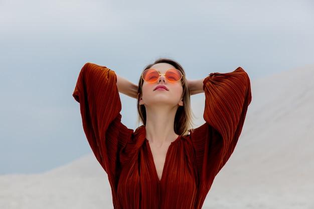 Mädchen in einer sonnenbrille und in einer burgunder-farbbluse auf einem weißen sand