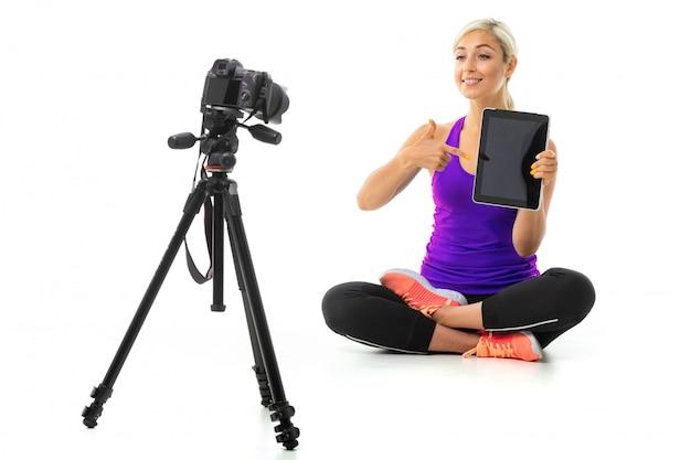 Mädchen in einer sportuniform sitzt vor der kamera mit tablette auf einem weißen hintergrund