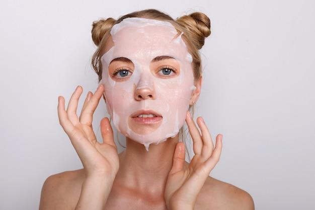 Mädchen in einer stoffmaske auf ihrem gesicht. kosmetologie