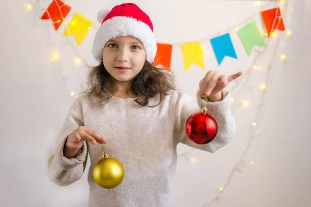 Mädchen in einer weihnachtsmütze hält weihnachtskugeln und lächelt