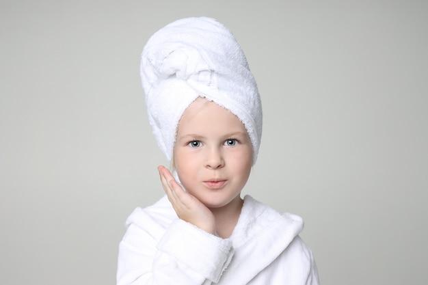 Mädchen in einer weißen robe und einem tuch auf ihrem kopf nach einer dusche und einem waschen ihrer haare