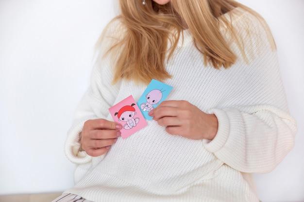 Mädchen in einer weißen strickjacke und in warmen socken, sitzend auf einem weichen kissen in einer skandinavischen art