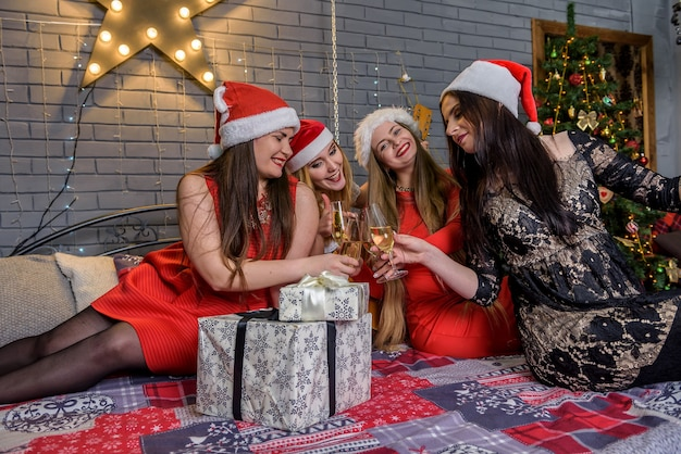 Mädchen in eleganten kleidern posieren im weihnachtsstudio