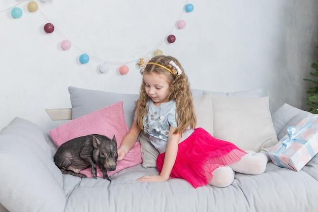 Mädchen in festlicher kleidung und mini schwein. schweinsymbol von 2019. schwarzes schwein als symbol für 2019 im chinesischen horoskop. haustier und kind. freundschaft und sorge für den jüngeren