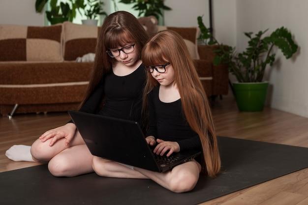 Mädchen in fitness-bodys sehen sich eine online-lektion auf einem laptop an und dehnen sich.