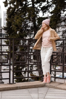 Mädchen in freizeitkleidung, brille und einem benie posiert in der stadt und schaut zur seite