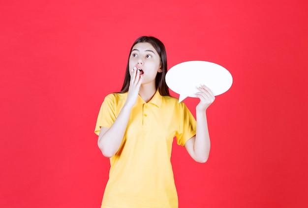 Mädchen in gelbem dresscode, das eine ovale infotafel hält und verängstigt und gestresst aussieht