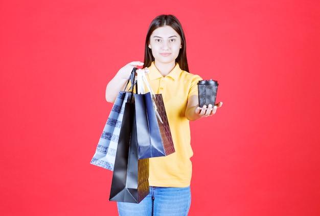 Mädchen in gelbem hemd, das mehrere blaue einkaufstaschen hält und dem kunden eine schwarze tasse getränk anbietet